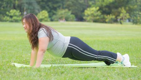 obese women push ups on grass