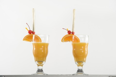 Two very delicious cocktails with slice of orange and cherry on it preparing for you