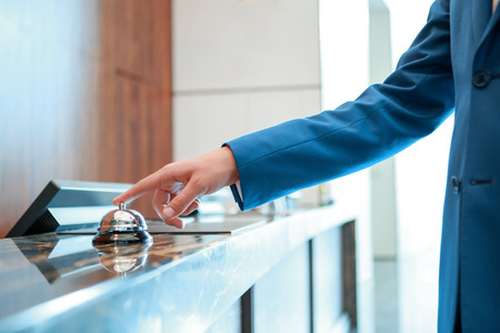 Service, please. Closeup of a businessman hand ringing silver service bell on hotel reception desk