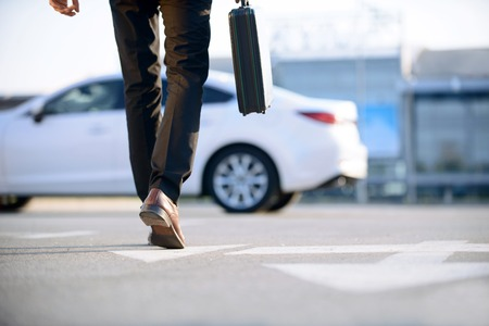 In pace of time. Modern young businessman holding case and going to his car while evincing confidence.