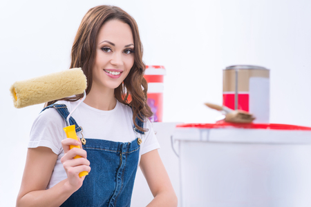 Girl with roller. Young attractive girl in male role is smiling and upholding a roller.