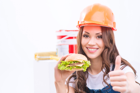 Lunch break. Smiling girl in male role is holding a burger and showing thumbs up.