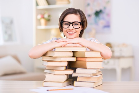 Girl with books. Young female student girl is leaning on a pile of her books and smiling.