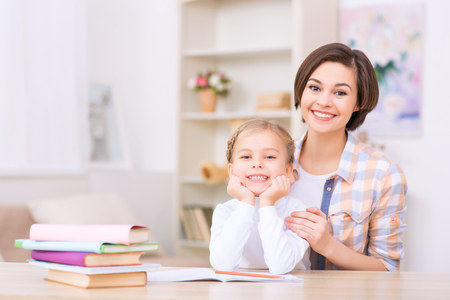 Genuine smiles. Young mom and her charming daughter are smiling radiantly while sitting at the desk.