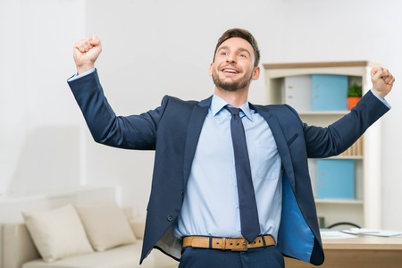 Feeling on the edge of glory. Full length of  overjoyed elated office worker holding his hands up and feeling content