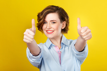 Foto de Everything is awesome. Shot of happy young woman cheerfully showing hand gesture and smiling. - Imagen libre de derechos