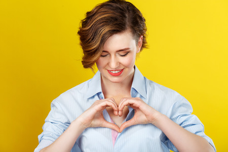 Photo for In my heart. Beautiful smiling woman is making a love gesture with her hands and looking happy. - Royalty Free Image