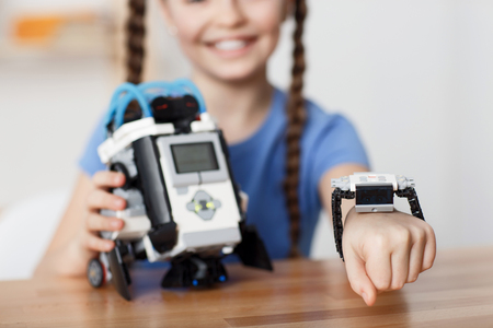 Photo pour Selective focus of hand of nice positive pretty girl sitting at the table and smiling while playing with robot - image libre de droit
