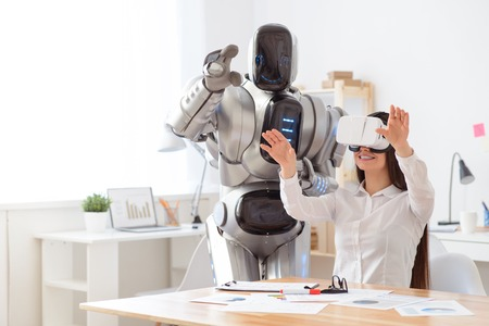 Photo pour Pleasant beautiful content girl sitting at the table and using virtual reality device while robot standing nearby - image libre de droit