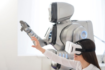 Photo pour Pleasant beautiful content woman holding hand in front of her and using virtual reality device while robot standing nearby - image libre de droit