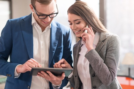 Photo pour Cheerful pleasant handsome man holding tablet and using it with his colleague who is talking on smart phone - image libre de droit
