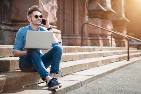 Nice to talk with you. Cheerful content handsome smiling guy sitting on he footsteps and using laptop while talking on cell phone