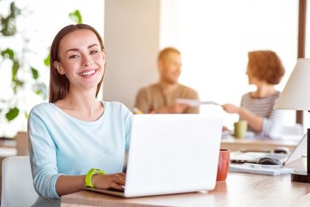 In a good mood.  Cheerful  delighted smiling woman sitting at the table and using laptop while her colleagues talking in the background