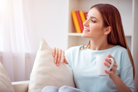 Live life fully.   Cheerful delighted beautiful woman looking in the window and drinking coffee while resting on the couch