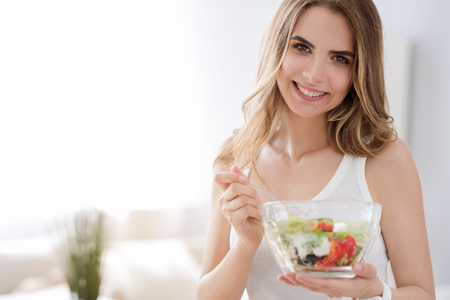 Photo for What I nee to be healthy. Pleasant delighted cheerful woman smiling and eating tasty vegetable salad while expressing joy - Royalty Free Image