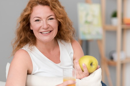 Think positively. Joyful beautiful adult woman holding apple and drinking juice while sitting on the couch