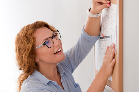 Involved in beloved work. Positive beautiful senior woman smiling and sticking calendar to the board while expressing joy