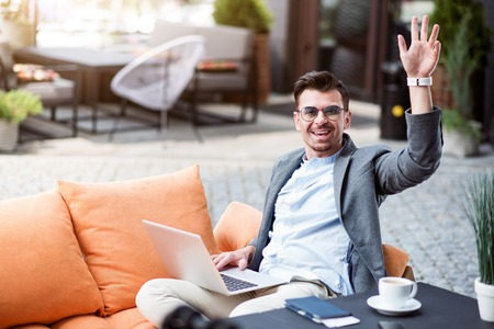 Come to me. Joyful delighted smiling man resting on the couch and using laptop while calling a waiter