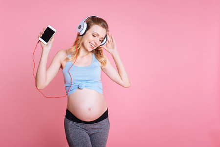 Listen and dance. Young pregnant sportswoman in training suit holding phone and singing song