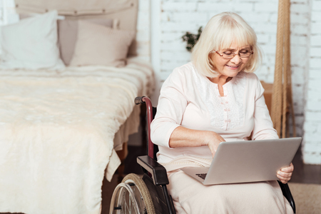 Modern granny. Pleasant delighted aged woman sitting in the wheelchair and using the Internet