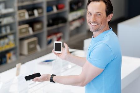 Cheerful man picking up new smartphone