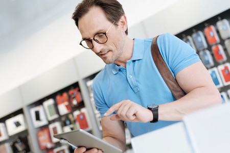Interested man testing technological capabilities of gadget at store