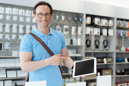 Smiling smart man pointing toward template digital tablet