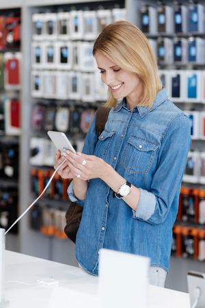 Radiant woman testing mockup smartphone at store