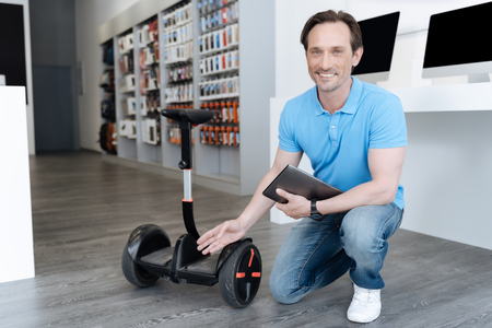 Salesman posing for camera with tablet and mini segway