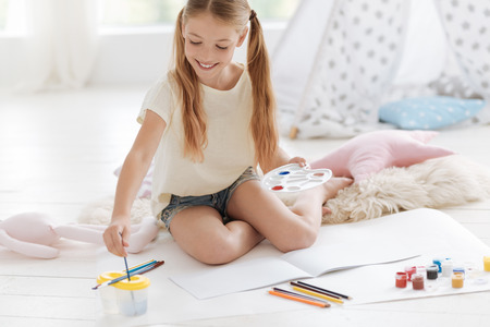 Talented girl sitting on floor and washing brushes while painting