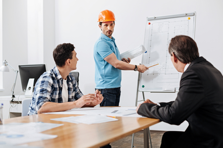 Young builder presenting a blueprint to his colleague