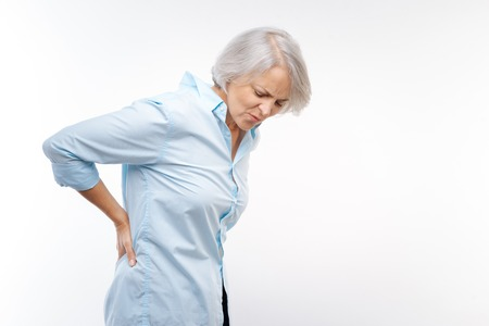 Photo pour Grey-haired woman suffering from pain in lower back - image libre de droit
