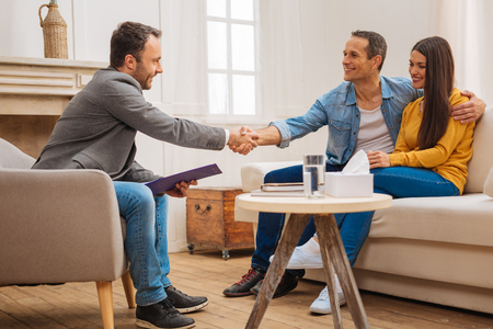Therapy works. Male psychologist shaking hands with husband who smiling and embracing his wife