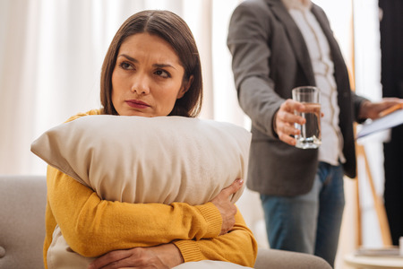 Bad association. Portrait of young upset pleasant woman who  looking aside refusing to drink water and hugging cushion