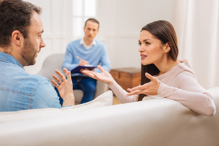 You annoy me.  Appealing mad female patient  shows her real emotion  while sitting next to husband and psychologist observing the situation