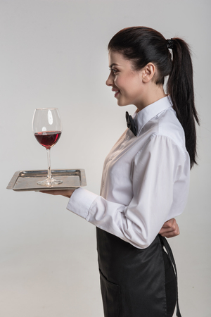 Your wine.  Skillful glad pensive  woman staying in profile and carrying salver where glass of wine put