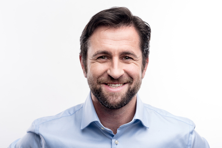 Foto de The portrait of a handsome dark-haired middle-aged man in a blue shirt smiling at the camera while posing against a white background - Imagen libre de derechos