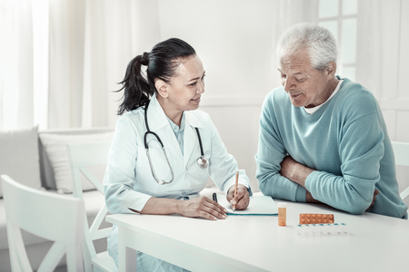 New recommendations. Mature pretty pleasant nurse sitting in the room by the table with her patient giving him advices and writing it.