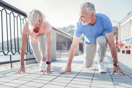 Photo pour Friendly competition. Joyful senior pleasant couple touching to the ground smiling and preparing to run across the quay. - image libre de droit