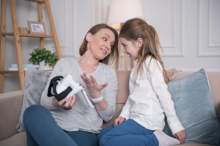 I love it. Loving cheerful mother sitting with her daughter and holding VR helmet