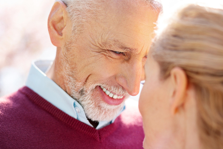 Sincere emotions. Portrait of a delighted senior man smiling while looking at his wife