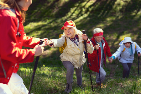 Photo for Great day. Inspired aged woman giving a hand and hiking with her friends - Royalty Free Image