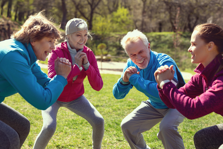 Foto de Staying healthy. Cheerful aged woman smiling and exercising with her friends in the park - Imagen libre de derechos