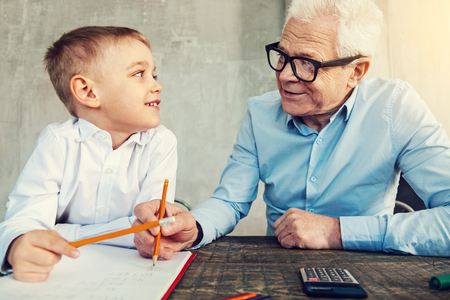 Foto de Clever grandfather. Happy smiling boy doing homework together with his helpful grandfather - Imagen libre de derechos