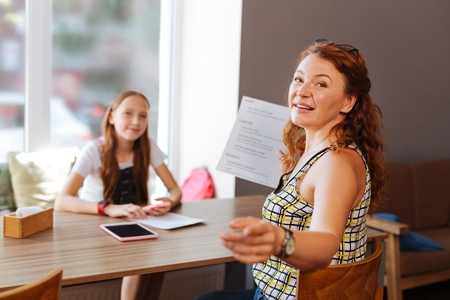 Red-haired appealing woman calling waiter in restaurant while having dinner with her daughter