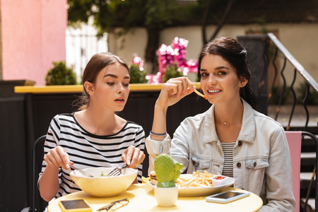 Feeling jealous. Dark-haired woman eating green garden salad feeling jealous while watching her friend eating fries