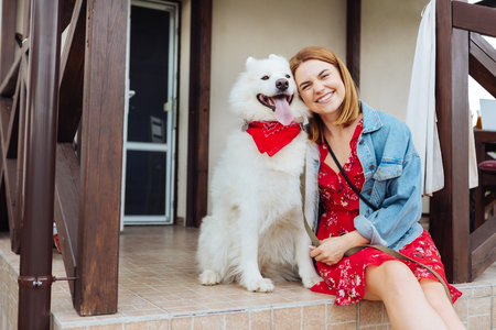 Woman with dog. Beaming fashionable woman feeling excited while coming to summer house with her dog