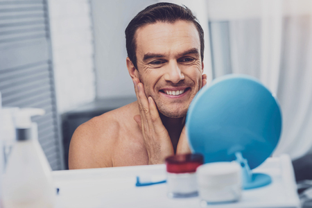 Beaming man. Beaming handsome man feeling relaxed while washing his face after long busy workday