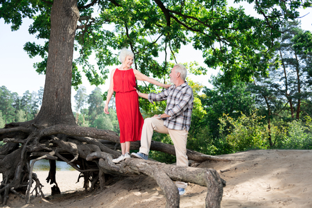 Leisure time. Beaming happy retired wife and husband feeling very memorable while spending leisure time in nature