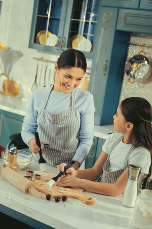 Mothers advices. Beautiful smiling young mother giving advices to her daughter teaching her how to cook